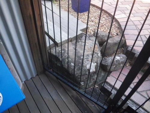 A large rock, timber sleepers & raised step are within 300mm of the base of the inside of a pool fence